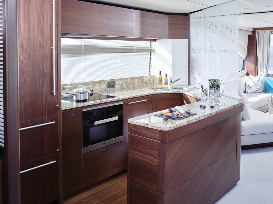 75-motor-yacht-interior-galley-sliding-panel-open-american-walnut-satin